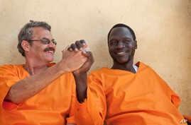 FILE - James Gatdet Dak, right, the longtime spokesman of opposition leader Riek Machar, clasps hands with William Endley, left, a South African former defense colonel who also worked with the opposition, as they prepare to be released from prison af