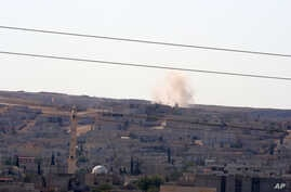 A mortar shelling lands as fighting intensified between Syrian Kurds and the militants of Islamic State in Kobani in Syria, in the background, in Mursitpinar near Suruc, Turkey, Oct. 4, 2014.