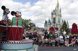 FILE - Visitors gather in front of Cinderella's castle to watch Mickey and Minnie Mouse during the Christmas parade at Walt Disney World's Magic Kingdom in Lake Buena Vista, Florida, Dec. 22, 2004.