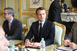 French President Emmanuel Macron flanked by Elysee general secretary Alexis Kohler, left, holds a meeting at the Elysee presidential Palace, in Paris, March 18, 2019. Macron summoned top security officials after police failed to contain rioting durin