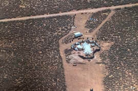 FILE - This Aug. 3, 2018, file photo released by Taos County Sheriff's Office, shows a rural compound in Amalia, N.M. Three women believed to be the mothers of 11 children found hungry and living in the filthy makeshift compound in rural northern New...