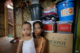 Typhoon survivor Emily Sagalis poses with baby Bea Joy inside her modest home near the Philippines' coastal city of Tacloban, Nov.5, 2014. Bea Joy was named for her grandmother, Beatrice, who died in the storm.