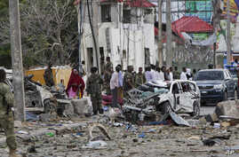 Security forces secure the scene next to destroyed vehicles following a suicide car bomb attack in the capital Mogadishu, Somalia, July 26, 2015.