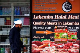 A man walks past a shop selling 'Halal meat' in the western Sydney suburb of Lakemba, September 25, 2014.
