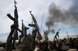 FILE - Rebel fighters hold up their rifles as they walk in front of a bushfire in a rebel-controlled territory in Upper Nile State, South Sudan February 13, 2014.