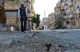 In this Tuesday, May 15, 2012 photo, a Syrian rebel walks in Khaldiyeh neighborhood in Homs province, central Syria.