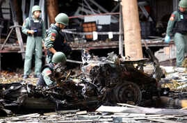 Thai bomb squad officers examine the wreckage of a car after an explosion outside a hotel in Pattani province, southern Thailand, Wednesday, Aug. 24, 2016.