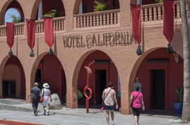 Tourists walk past Hotel California in the town of Todos Santos, Baja California Sur, Mexico, May 2, 2017.