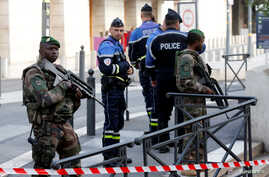 French police and soldiers secure a street near the Saint-Charles train station after French soldiers shot and killed a man who stabbed two women to death at the station, in Marseille, France, Oct. 1, 2017.