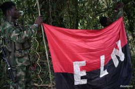 FILE - Rebels of the National Liberation Army (ELN) hold a banner in the northwestern jungles in Colombia, Aug. 30, 2017.