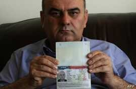 Fuad Sharef Suleman shows his US immigrant visa in Arbil, the capital of the Kurdish autonomous region in northern Iraq, on January 30, 2017 after returning to Iraq from Egypt, where him and his family were prevented from boarding a plane to the U.S....