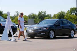 FILE - A pedestrian crosses in front of a vehicle as part of a demonstration at the Mcity test facility at the University of Michigan in Ann Arbor, July 20. Automakers say cars that wirelessly talk to each other hold the potential to dramatically red