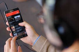 FILE - The YouTube Music app is displayed on a mobile phone in Los Angeles, Nov. 13, 2015.