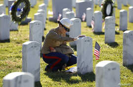 FILE - A female U.S. Marine touches the grave of a friend at Arlington National Cemetery in Virginia.