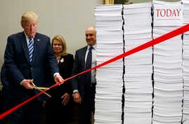 """President Donald Trump cuts a red tape during an event on federal regulations at the White House, Dec. 14, 2017, in Washington. """"Let's cut the red tape, let's set free our dreams,"""" Trump said, next to stacks of paper that he said represented the size"""