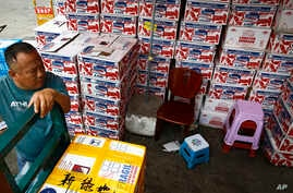 A man waits for the goods to be load on his tricycle at a dealer selling imported seafoods at the Jingshen seafood market in Beijing, Thursday, July 12, 2018.