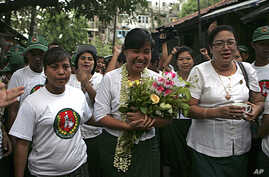 Le Le Aye, center, a candidate of the military-backed Union Solidarity and Development Party (USDP), waves to supporters during her campaign for the April 1 by-election in Rangoon, Burma, March 29, 2012.