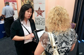 In this May 30, 2012 photo, Mi-Ran Park-Wong, of Macy's, speaks to a job applicant during a career expo sponsored by Jobs Direct USA in Orlando, Fla.