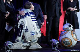 """Mark Hamill, a cast member of the movie """"Star Wars: The Last Jedi,"""" hugs character R2-D2 during  promotional event in Tokyo, Dec. 6, 2017."""