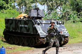 A government troop gestures as he passes an armoured personnel carrier posted along a main highway of Pantar town, Lanao Del Norte, after residents start to evacuate their hometown of Marawi city, southern Philippines, May 24, 2017.