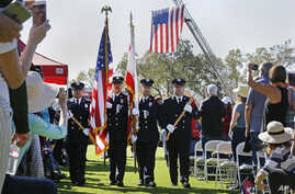 A U.S. flag hangs from the ladder of a firetruck as a color guard made up of Santa Rosa firefighters presents the colors to start a Day of Remembrance memorial for victims of California wildfires, in Santa Rosa, Oct. 28, 2017.