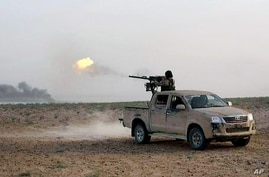 In a picture released May 20, 2015, by the website of Islamist militants, an Islamic State fighter fires his weapon during a battle against Syrian government forces on a road between Homs and Palmyra, Syria.