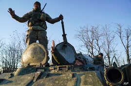 Ukrainian soldiers stand atop an armored personnel carrier near Urzuf on the south coast of Azov sea, eastern Ukraine, Nov. 29, 2018.