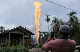FILE - A man takes pictures of a burning oil well in Pasir Putih village in eastern Aceh, Indonesia, April 25, 2018. The newly drilled, unregulated oil well in western Indonesia exploded into flames early Wednesday, burning to death a number of peopl