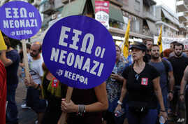 """Demonstrators hold placard reading ''Neo-Nazis out"""" during protest against the stabbing of Pavlos Fyssas, who died early Wednesday, in the suburb of Nikaia, near Athens, Sept. 19, 2013."""