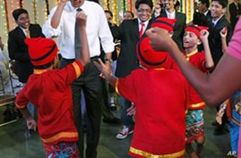 President Barack Obama and first lady Michelle Obama dance with students as they celebrate Diwali, a revered festival, during a visit to Holy Name High School in Mumbai, India, Sunday, Nov. 7, 2010. (AP Photo/Charles Dharapak)