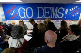 FILE - Democratic Party volunteers get instructions for canvassing neighborhoods, Nov. 4, 2016, following a get-out-the-vote rally at a campaign office in Seattle.