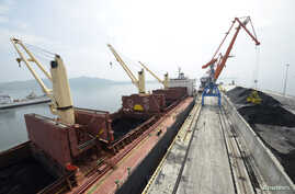 A cargo ship is loaded with coal during the opening ceremony of a new dock at the North Korean port of Rajin, July 18, 2014.