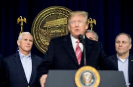 President Donald Trump, accompanied by Vice President Mike Pence, left, and House Republican Majority Whip Steve Scalise, R-La., right, speaks to members of the media after participating in a Congressional Republican Leadership Retreat at Camp David,