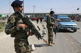 In this  July 10, 2018 photo, an Afghan national army soldier stops a car  at a temporary checkpoint on the outskirts of Kabul, Afghanistan.