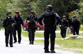 Law enforcement officials search a street near the Clinton Correctional Facility in Dannemora, New York, from which two convicts broke out about a week ago, June 10, 2015.
