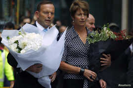 Australian Prime Minister Tony Abbott and his wife Margie prepare to place floral tributes  near the cafe in central Sydney, December 16, 2014, where hostages were held for over 16-hours.