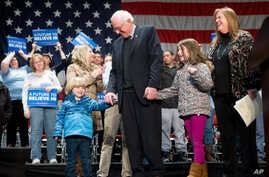 Democratic presidential candidate Sen. Bernie Sanders, I-Vt., center, is joined by his wife Jane, right, and grandchildren, Dylan, 4, and Ella, 7, on stage after speaking at a town hall at the Orpheum Theater in Sioux City, Iowa, Jan. 19, 2016.