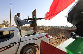 A Libyan rebel fighter aims his heavy machine gun towards forces loyal to Libya's leader Moammar Gadhafi at Misrata's western front line, some 25 kilometers from the city center, May 26, 2011.