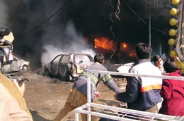 FILE - Vehicles are on fire after a blast in Peshawar, Pakistan, Dec. 5, 2009.
