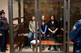 Feminist punk group Pussy Riot member Yekaterina Samutsevich sits in a glass cage at a court room in in Moscow, Wednesday Oct. 10, 2012. Moscow appeals court has freed Yekaterina Samutsevich of jailed Pussy Riot members but upholds the prison sentenc