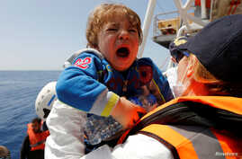 A child migrant is brought onto the Malta-based NGO Migrant Offshore Aid Station (MOAS) ship Phoenix during a rescue operation in the central Mediterranean, in international waters off the Libyan coastal town of Sabratha, May 4, 2017.