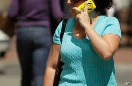 FILE - A woman talks on her cellphone while walking along First Street in San Francisco. NTP scientists and the U.S. Food and Drug Administration say current safety limits on cellphone radiation are protective.