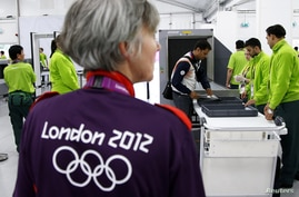 Indian shooting team member Sanjeev Rajput holds his laptop as he goes through a security check at the Welcome Center near the Athletes' Village at the Olympic Park in London, July 18, 2012.