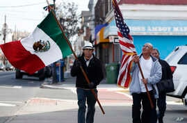 Members of the Mexican Association of Perth Amboy carry flags while taking part in an immigration protest, in Perth Amboy, New Jersey, Feb. 16, 2017.