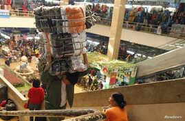 A man carries a bag of clothes at Dong Xuan market in Hanoi December 21, 2012. Vietnam is estimated to have a trade deficit of $200 million in December, while its annual trade balance will be at a surplus of $284 million, a state-run newspaper report