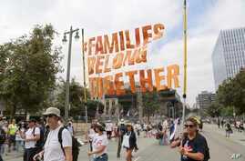 """FILE - Demonstrators hold signs as they participate in the """"Families Belong Together: Freedom for Immigrants"""" march, June 30, 2018, in Los Angeles. In major cities and tiny towns, marchers gathered across America, moved by accounts of children separa..."""