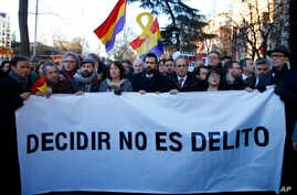 "The president of Catalonian Parliament, Roger Torrent, center, and the Catalan regional President Quim Torra, center right, hold a placard that reads in Spanish: "" To Choose is not a Crime"", outside the Spanish Supreme Court in Madrid, Tuesday, Feb."