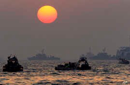 The orange sun begins to set as searchers and divers look for bodies of passengers believed to have been trapped in the sunken ferry Sewol in the water off the southern coast near Jindo, south of Seoul, South Korea, April 22, 2014.
