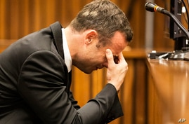 Oscar Pistorius, puts his hand to his face while listening to evidence from a witness speaking about the morning of the shooting in court on the fourth day of his trial at the high court in Pretoria, South Africa, March 6, 2014.