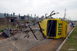 Power lines and a passenger bus are seen after being damaged by strong winds caused by Cyclone Hudhud in the southern Indian city of Visakhapatnam Oct. 13, 2014.